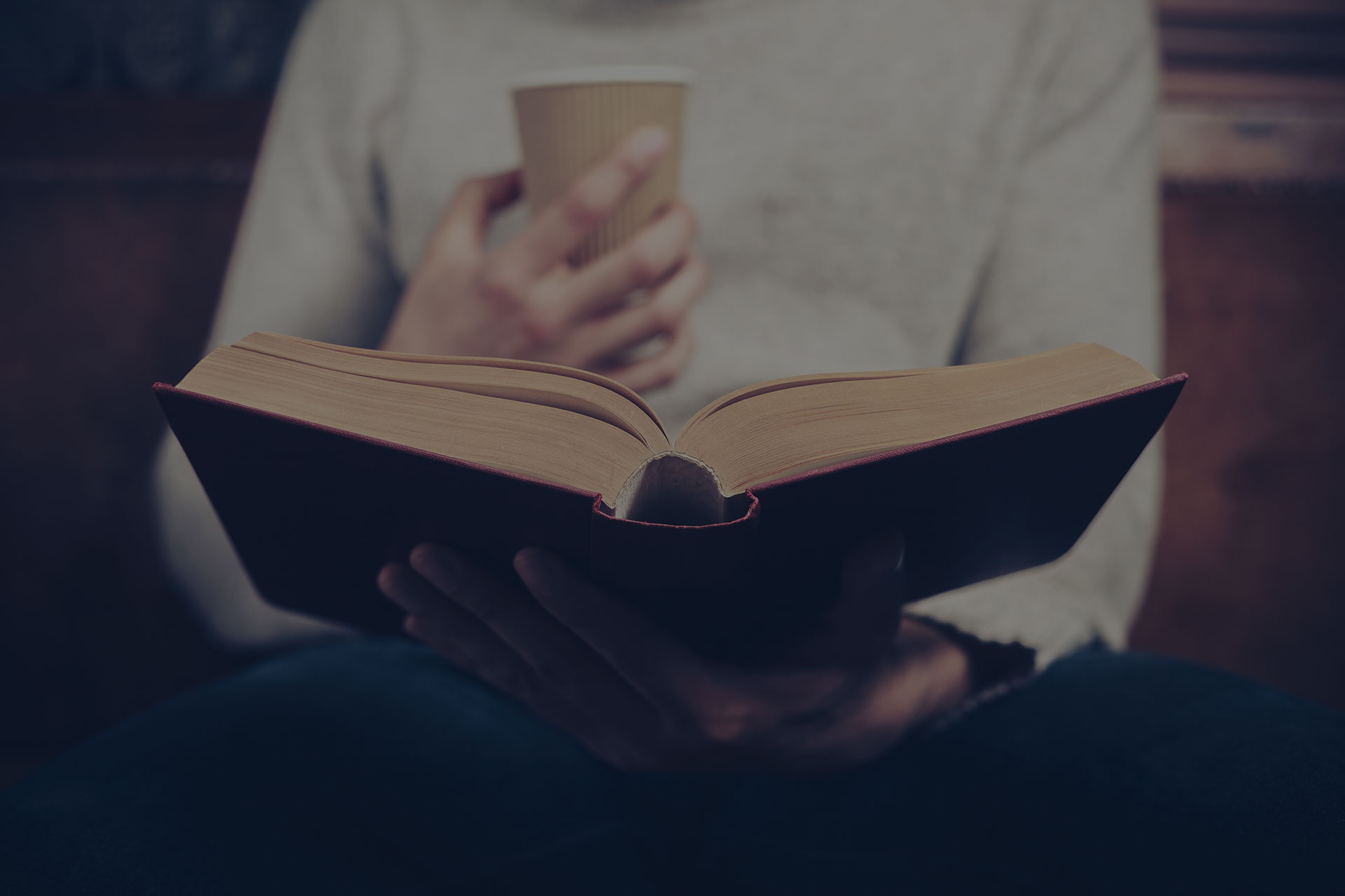 Man reading from book with coffee
